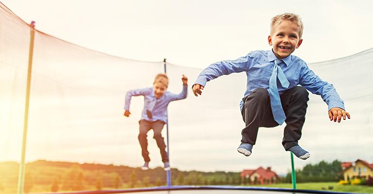 Jungen in Krawatten springen Trampolin