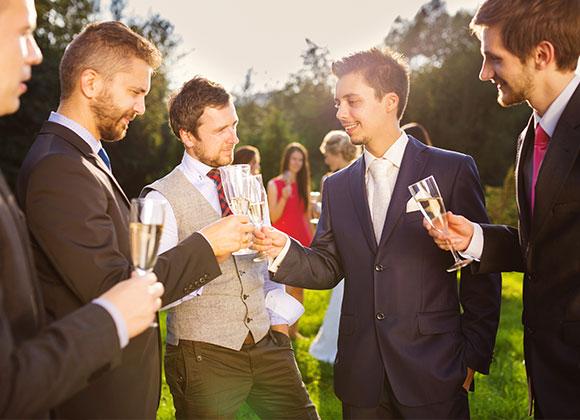 Hochzeitsgäste in Anzügen stoßen an