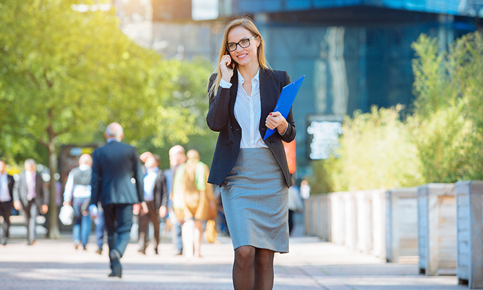 Business Women in Bodybluse spricht in ihr Handy