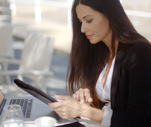 Dresscodes Damen - Business Attire Sommer. Geschäftsfrau arbeite an Laptop und Tablet.