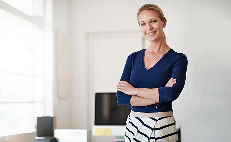 Frau steht im Büro und lächelt in die Kamera