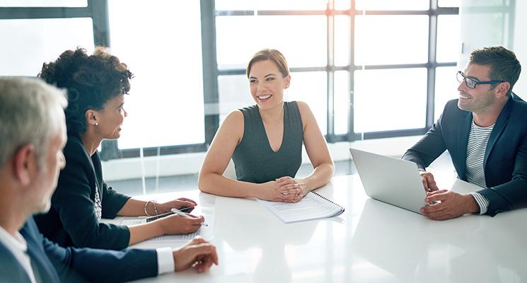 Women in Business Insights - Frau sitzt mit Kollegen am Tisch in einem Meetingraum.