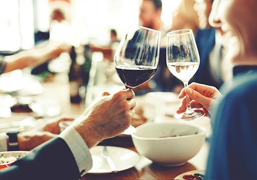 Eine Frau und ein Mann stoßen mit ihren Weingläsern an