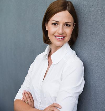 Business Frau lehnt in weißer Hemdbluse an einer Wand