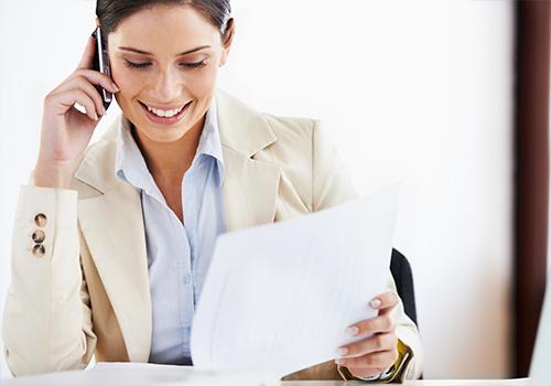 Frau telefoniert am Schreibtisch und blättert in Unterlagen.