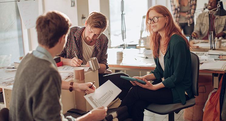 Eine Frau diskutiert mit zwei Kollegen am Schreibtisch