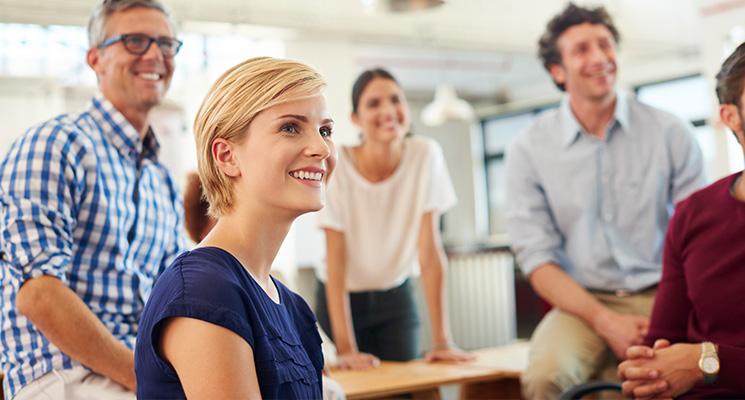 Ein Team aus Kollegen und Kolleginnen lächelt und schaut zufrieden