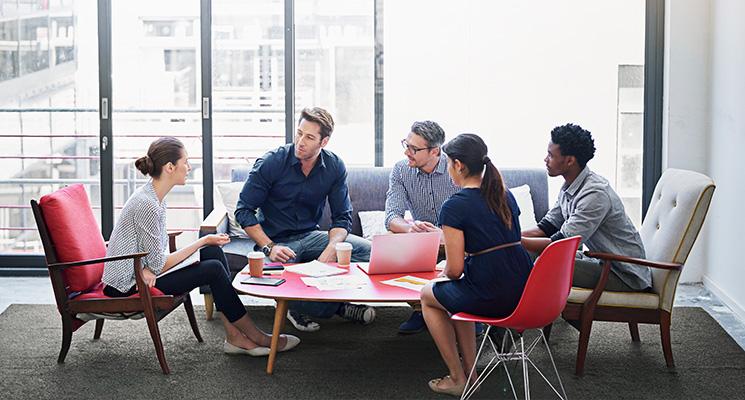 Frauen und Männer sitzen gemeinsam am Tisch und beraten sich