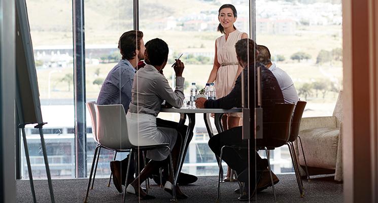 Eine Gruppe Männer und Frauen diskutieren am Tisch über Geschäftliches