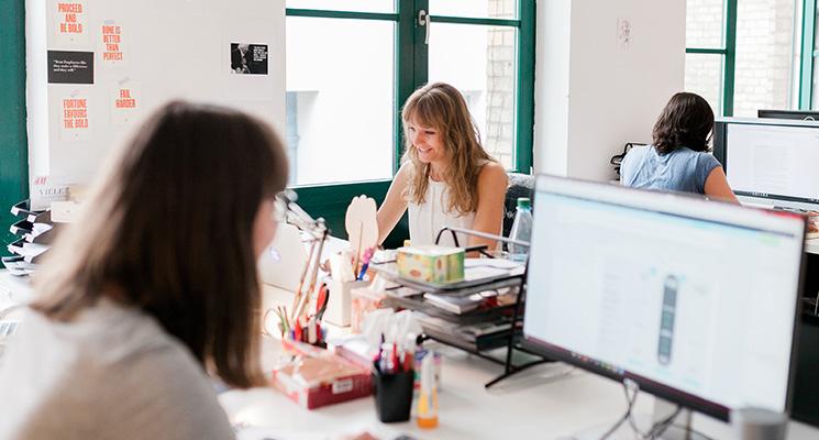 Kolleginnen, die am Schreibtisch sitzen