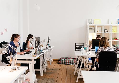 Vier Frauen sitzen in einem großen, hellen Büro am Schreibtisch