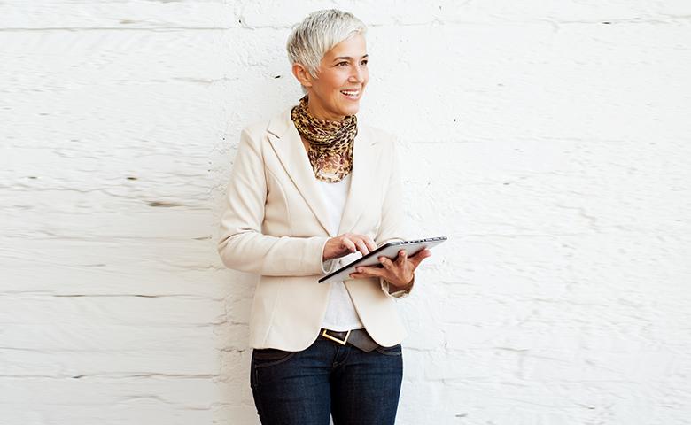 Frau lehnt, mit einem iPad in der Hand, lächelnd an einer weißen Wand