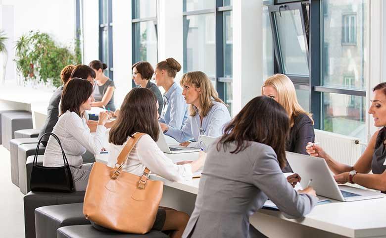 Women In Business Insights - Ein Gruppe von Frauen im Meetingraum