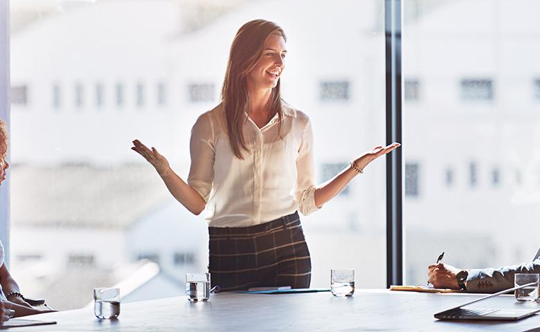 Frau steht am Meetingtisch gehobenen Händen und lächelt