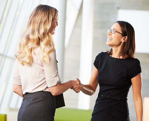 Women In Business Insights - Zwei Frauen schütteln zufrieden die Hände