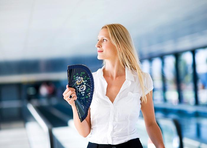 Frau mit weißer Business Sommerbluse fächert sich Abkühlung zu