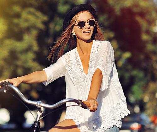 Frau in Tunika fährt Fahrrad - Blusentypen