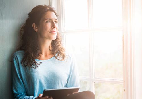 Women in Business Insights - Frau sitzt nachdenklich am Fenster.