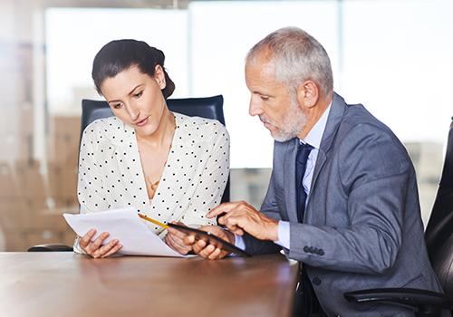 Frau und Mann besprechen Unterlagen im Meetingraum.