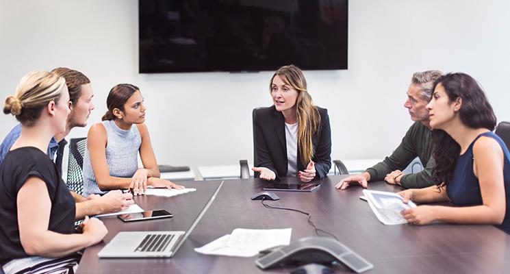 Frauen sitzen an einem großen Meetingtisch und reden