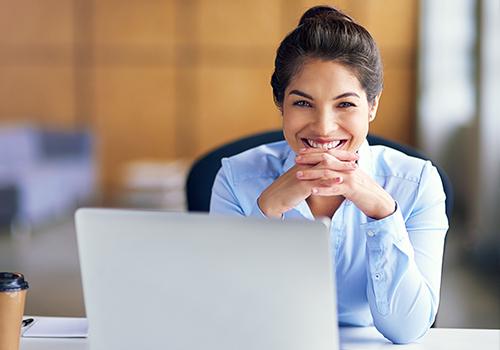 Frau sitz am Schreibtisch und lächelt über Ihren Laptop hinweg