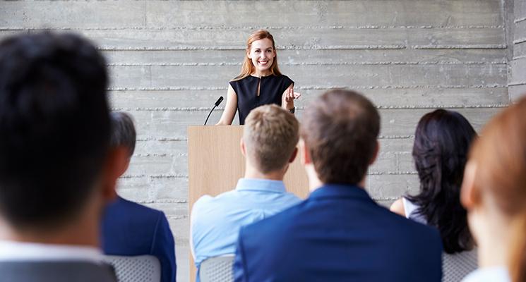 Frau steht am Rednerpult und spricht vor Publikum